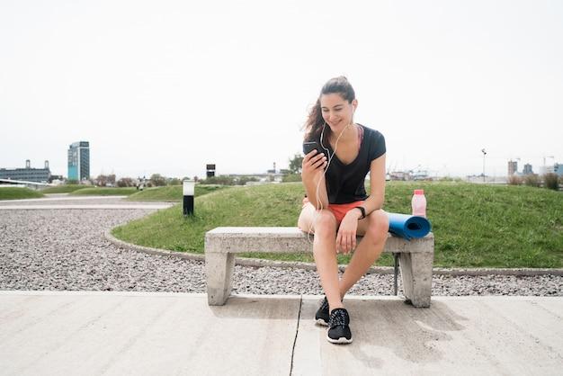 Atletische vrouw die haar telefoon met behulp van