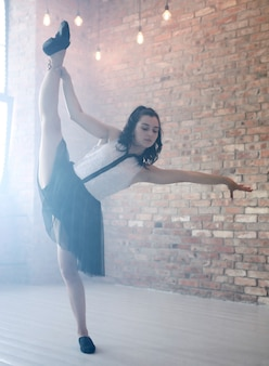 Atletische vrouw die het gymnastiek- uitrekken doet