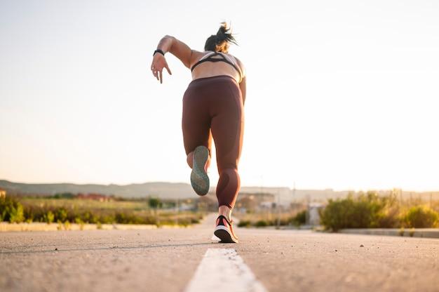 Atletische vrouw die in de straat loopt