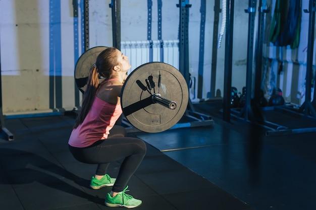 Atletische vrouw die met een barbell in de gymnastiek uitoefent