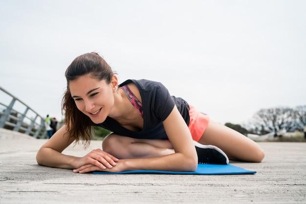 Atletische vrouw die oefening met yogamat doet