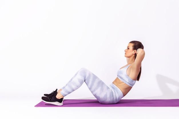 Atletische vrouw die op mat ligt en traint en sit-ups doet die buikspieren trainen
