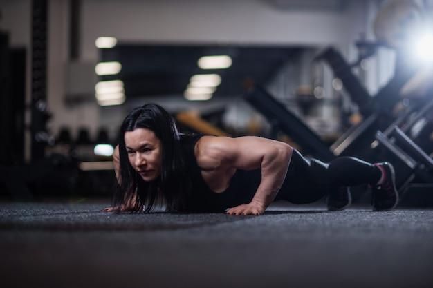 Atletische vrouw die opdrukoefeningen in de gymnastiek doet