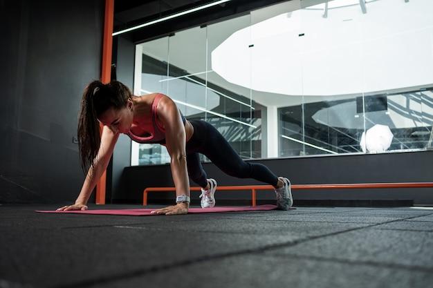Atletische vrouw die push-ups uitvoert tijdens training in de sportschool