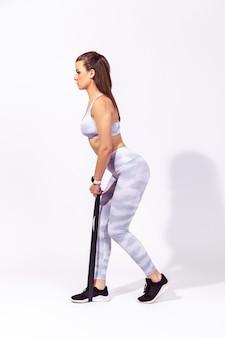Atletische vrouw die sport doet, op rubberen streep staat om benen te trainen, rubberen expander uit te oefenen