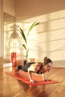 Atletische vrouw die sportoefeningen in een studio doet