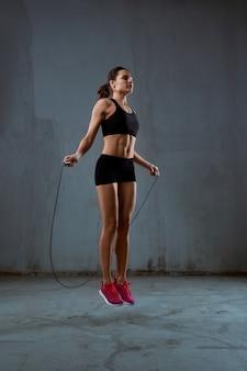 Atletische vrouw die springtouw gebruikt