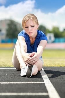 Atletische vrouw die uitrekkende oefening op buitenshuis doet