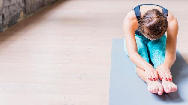 Atletische vrouw die uitrekkende oefening op yogamat doet