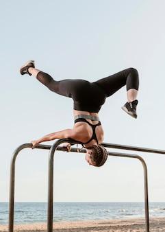 Atletische vrouw doet fitness oefeningen buiten aan het strand