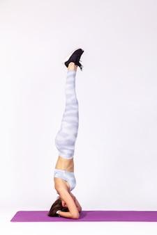 Atletische vrouw doet yoga hoofdstand pose op mat, gymnastiek voor lichaamsbalans en flexibiliteit.
