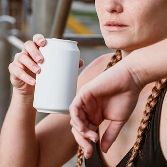 Atletische vrouw frisdrank buiten drinken na het trainen