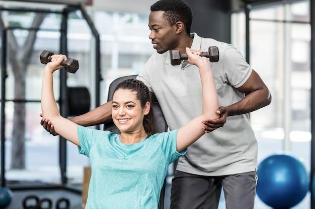 Atletische vrouw het opheffen gewichten die door trainer bij gymnastiek worden geholpen