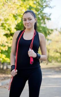 Atletische vrouw in een park in haar sportkleding met een springtouw bungelend om haar nek