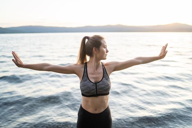 Atletische vrouw in een sport-bh en zwarte legging strekt zich uit voordat ze lessen begint aan de avondoever van het meer