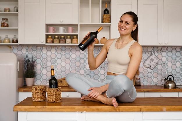 Atletische vrouw in een trainingspak in een lichte keuken drinkt rode wijn uit een fles na het sporten. vrouw glimlacht en kijkt naar de camera