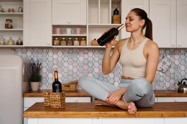Atletische vrouw in een trainingspak in een lichte keuken drinkt rode wijn uit een fles na het sporten.