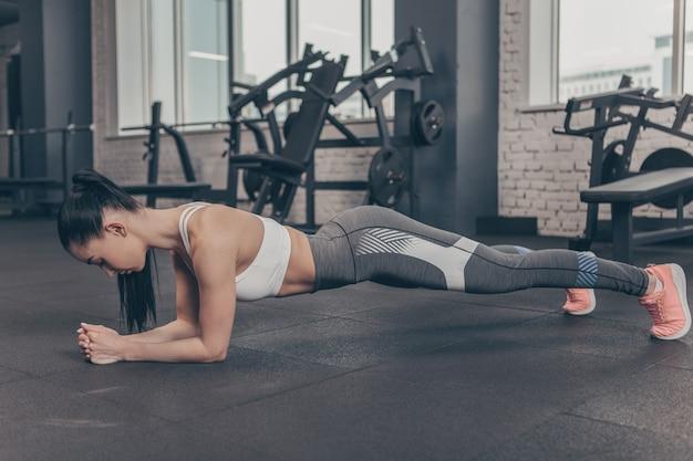 Atletische vrouw in sportenbustehouder en beenkappen die plankoefening doen bij de gymnastiek, exemplaarruimte