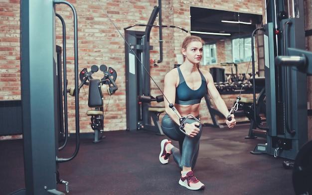 Atletische vrouw in sportkleding die oefening in een crossovermachine doen in de gymnastiek.