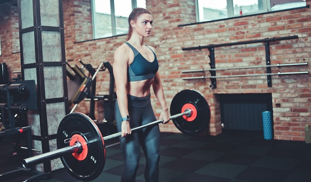 Atletische vrouw in sportkleding houdt een zware halter in de sportschool. trainingsconcept, gewichtheffen