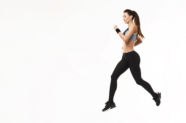 Atletische vrouw in sportkleding opleiding draait op wit.