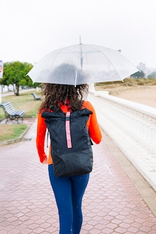 Atletische vrouw met masker en paraplu in de straat
