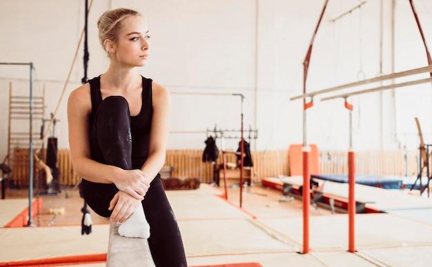 Atletische vrouw ontspannen na gymnastiek training met kopie ruimte