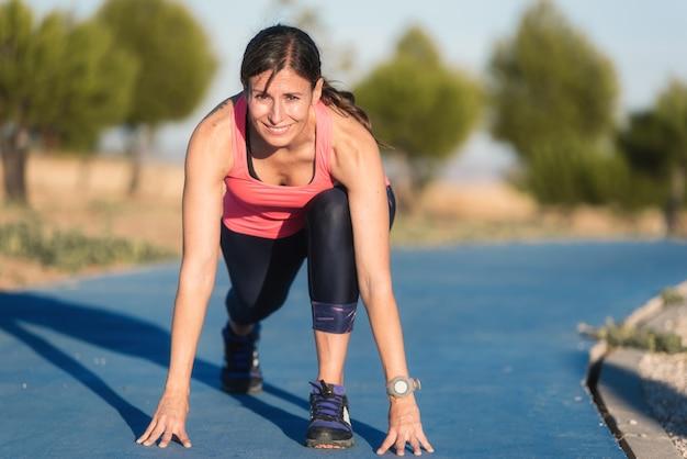 Atletische vrouw op renbaan die bereid om looppas te beginnen worden.