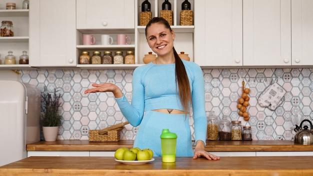 Atletische vrouw praat over gezond eten in de keuken en lacht. op tafel staan groene appels en een groene fles voor een sportdrankje en water