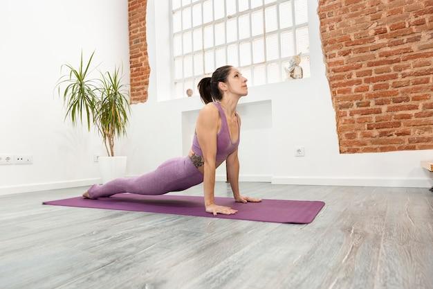 Atletische vrouw training en het beoefenen van een yogales vanuit huis. ruimte voor tekst.