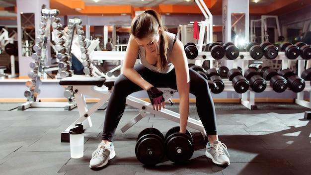 Atletische vrouw training met halters in de sportschool