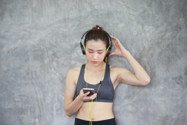Atletische vrouwen die het luisteren muziek uitvoeren die zich tegen muur bij geschiktheidsgymnastiek bevinden