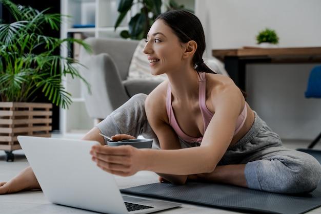Atletische vrouwentrainer die thuis op een trainingvideo online op laptop letten
