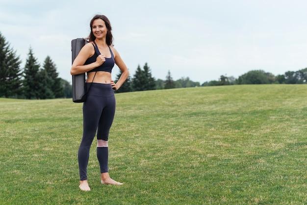 Atletische yogavrouw die in openlucht stellen