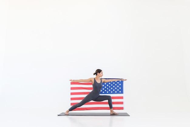 Atletische yogi-vrouw beoefent yoga op mat die in oorlogshouding staat met amerikaanse vlag op witte scène met vrije ruimte