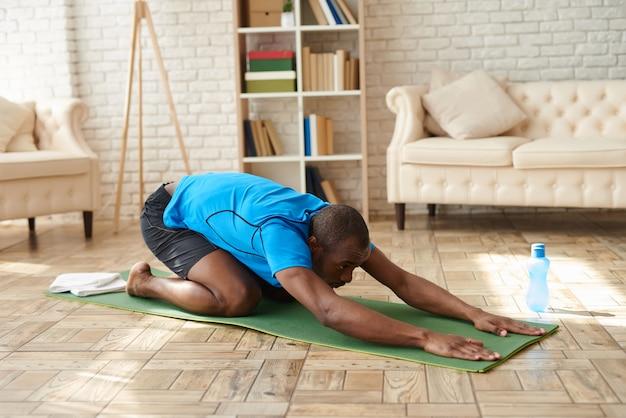 Atletische zwarte man doet geavanceerde yoga op mat thuis.