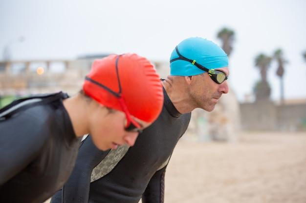 Atletische zwemmers in wetsuits op het strand