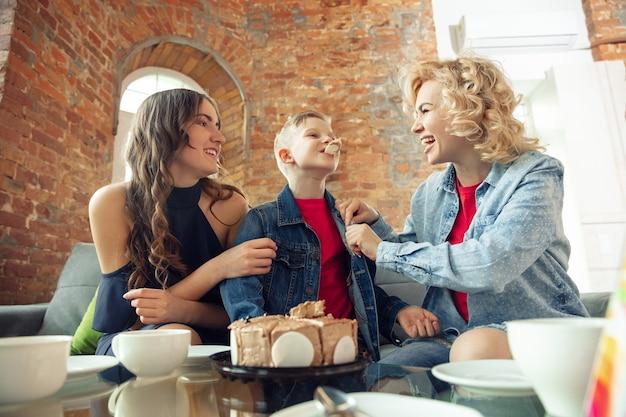 Atmosfeer. moeder, zoon en zus hebben thuis plezier. vakantie, familie, comfort, gezellig concept, verjaardag vieren. mooie kaukasische familie. tijd samen doorbrengen, spelen, lachen groet