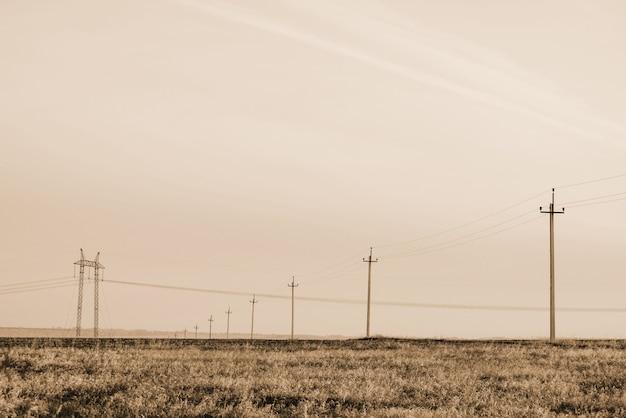 Atmosferisch landschap met hoogspanningslijnen in veld onder hemel in sepia tinten. achtergrondafbeelding van elektrische pijlers met copyspace. hoogspanningsdraden boven de grond. elektriciteitsindustrie in zwart-wit.