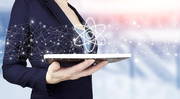 Atoommolecuul als concept voor wetenschap. hand houden witte tablet met digitale hologram molecuul atoom teken op lichte onscherpe achtergrond. moleculaire structuur op atomair niveau.