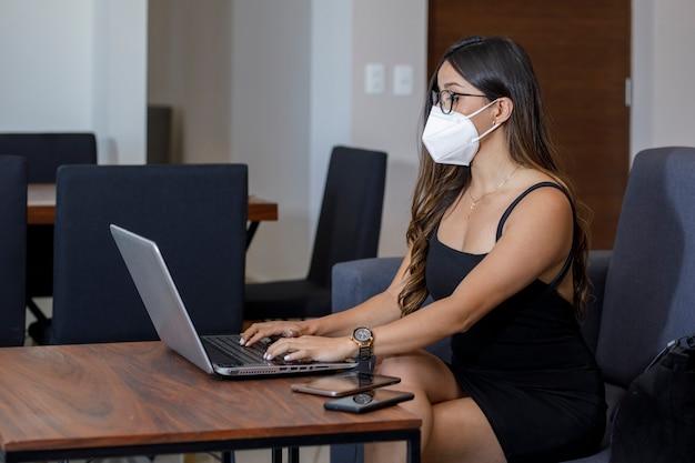 Atractiva mujer empresaria con mascarilla trabajando en su ordenador desde casa
