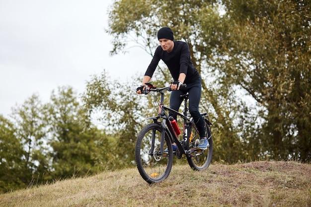 Attaractieve man met zwart pak en pet rijden dowhill op zijn mountainbike, met cardio-training, genieten van zijn recreëren in open lucht en prachtige natuur. sport, gezond levensstijlconcept.