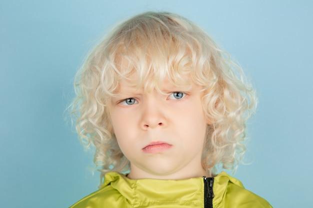 Attent. close-up portret van mooie kaukasische kleine jongen geïsoleerd op blauwe muur. blond krullend mannelijk model. concept gezichtsuitdrukking, menselijke emoties, kinderjaren,