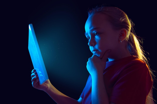 Attent. kaukasisch meisje portret op donkere studio achtergrond in neonlicht. mooi vrouwelijk model dat tablet gebruikt.