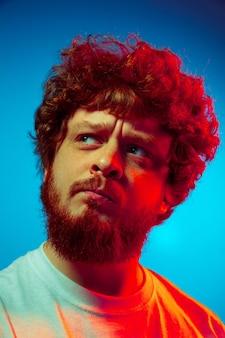 Attent. kaukasische close-up man portret geïsoleerd op blauwe muur in rood neonlicht. mooi mannelijk model, rood krullend haar. concept van menselijke emoties, gezichtsuitdrukking, verkoop, advertentie.