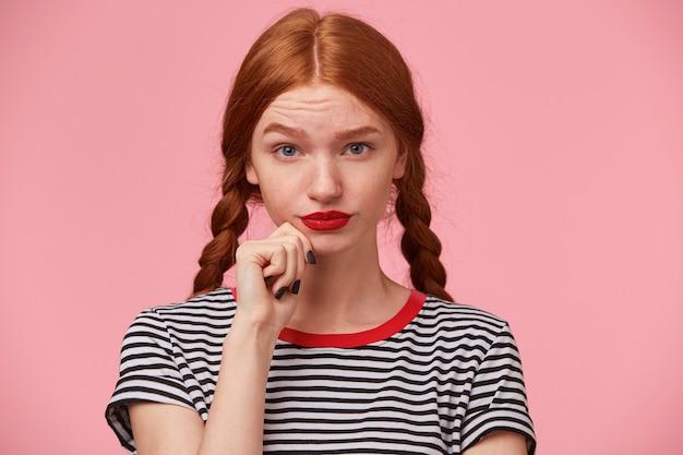 Attent mooi roodharig meisje met twee vlechten houdt vuist bij de kin en kijkt sceptisch, met verdacht en wantrouwen, twijfelachtig, geïsoleerd op roze muur
