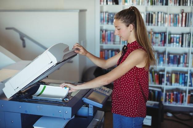 Attent schoolmeisje dat xerox-fotokopieerapparaat in bibliotheek gebruikt Premium Foto