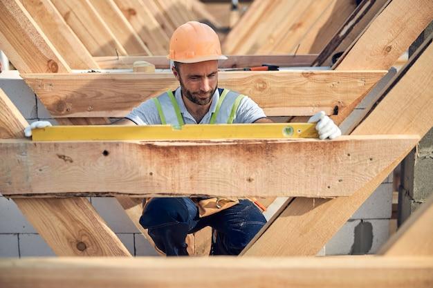 Attente bouwer die een waterpasinstrument gebruikt tijdens het meten van een houten oppervlak van een dak