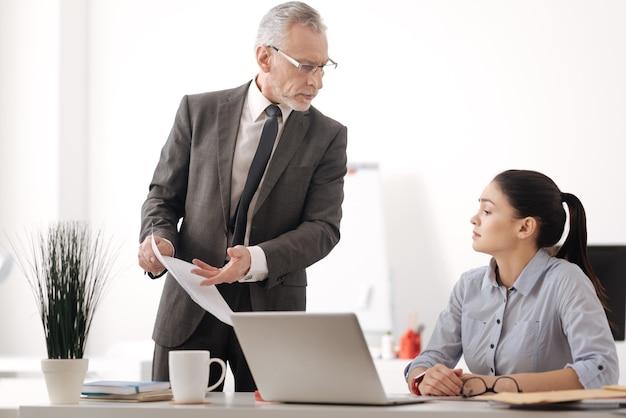 Attente brunette zit in halve positie op haar werkplek documenten te kijken terwijl ze diep in gedachten is
