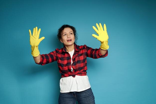 Attente en geconcentreerde spaanse vrouw kijkt naar haar handen in gele rubberen handschoenen voor huishoudelijk werk en doet alsof ze vuil op een onzichtbaar oppervlak aanraakt en onderzoekt